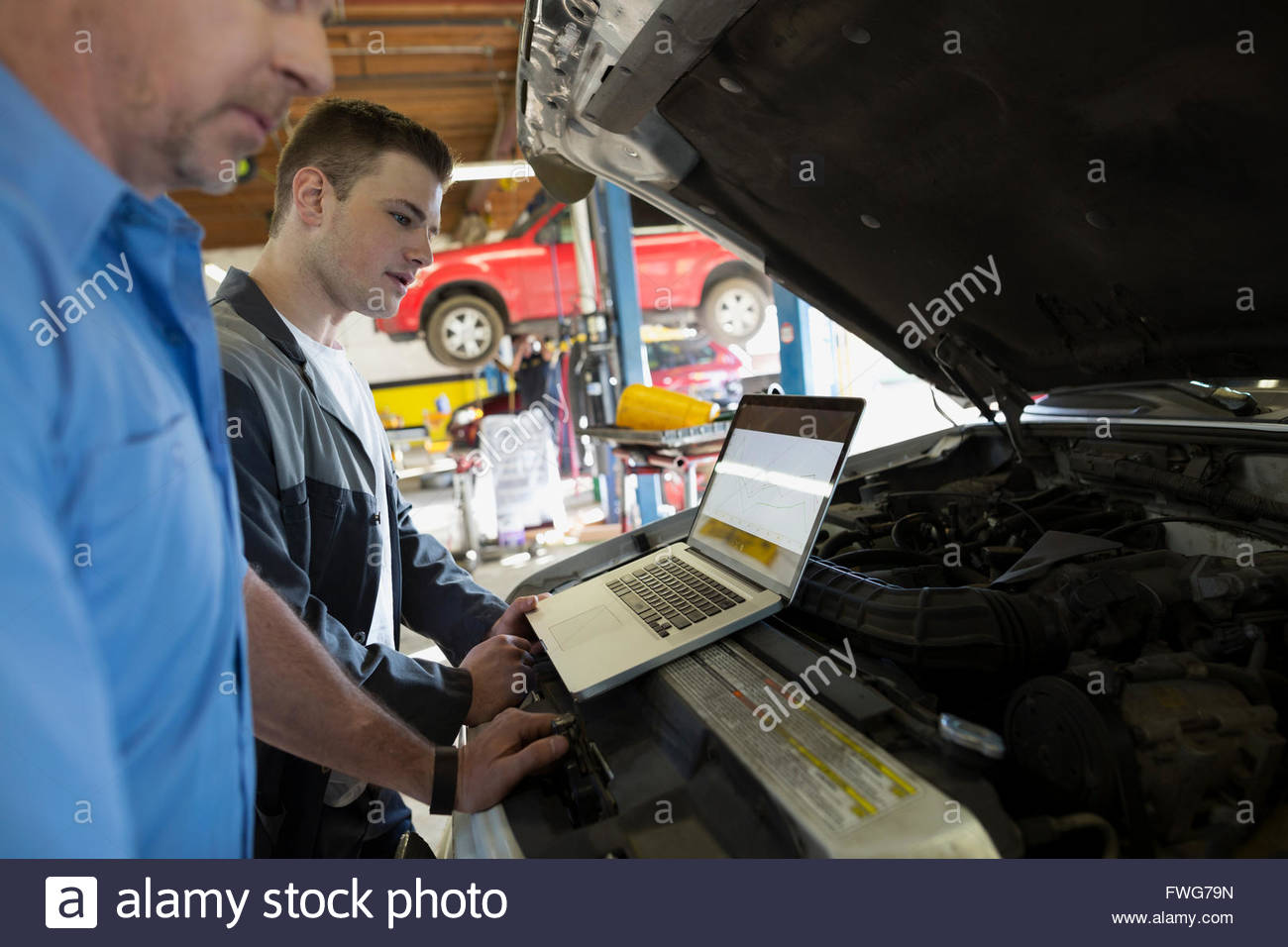 Mechanics with laptop performing engine diagnostics - Stock Image