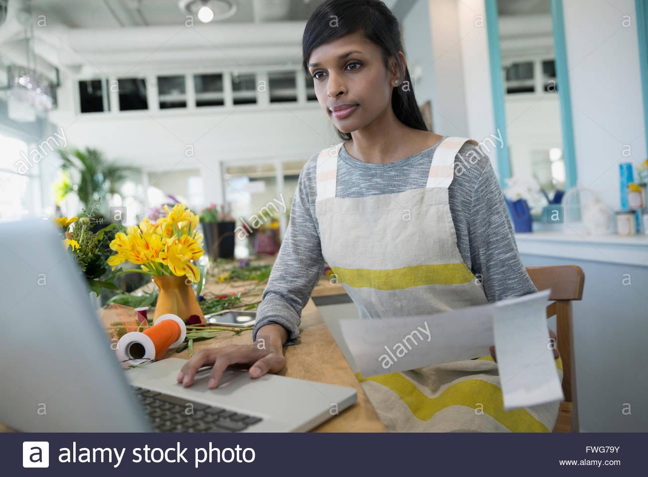 Florist using laptop in flower shop - Stock Image