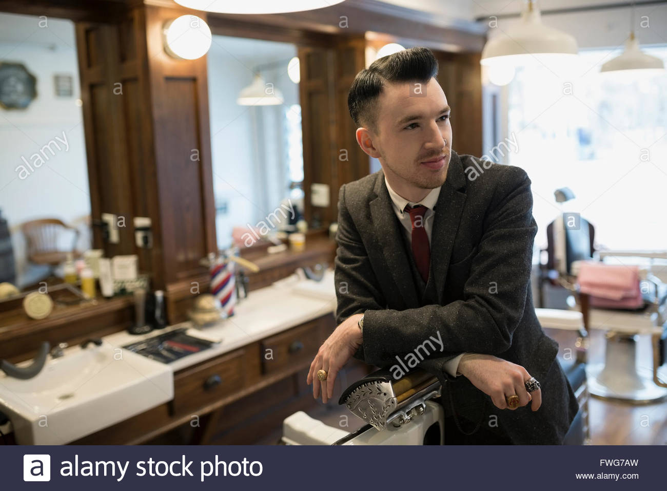 Confident barber wearing suit in barber shop - Stock Image