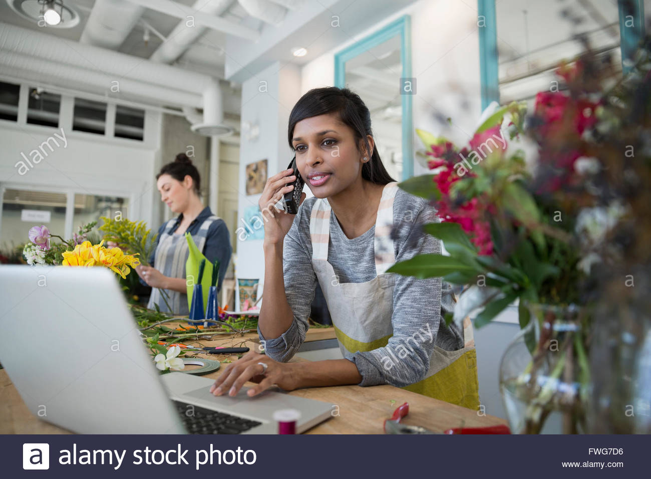 Florist talking on telephone at laptop flower shop - Stock Image