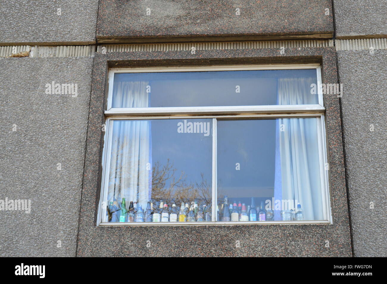 A grotty student window with bottles of alcohol lined up. Student life.  Exterior shot. Concrete decaying building - Stock Image