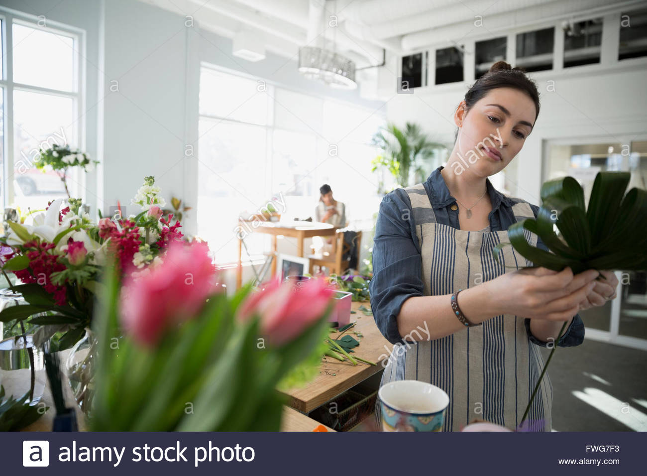 Florist arranging bouquet in flower shop - Stock Image