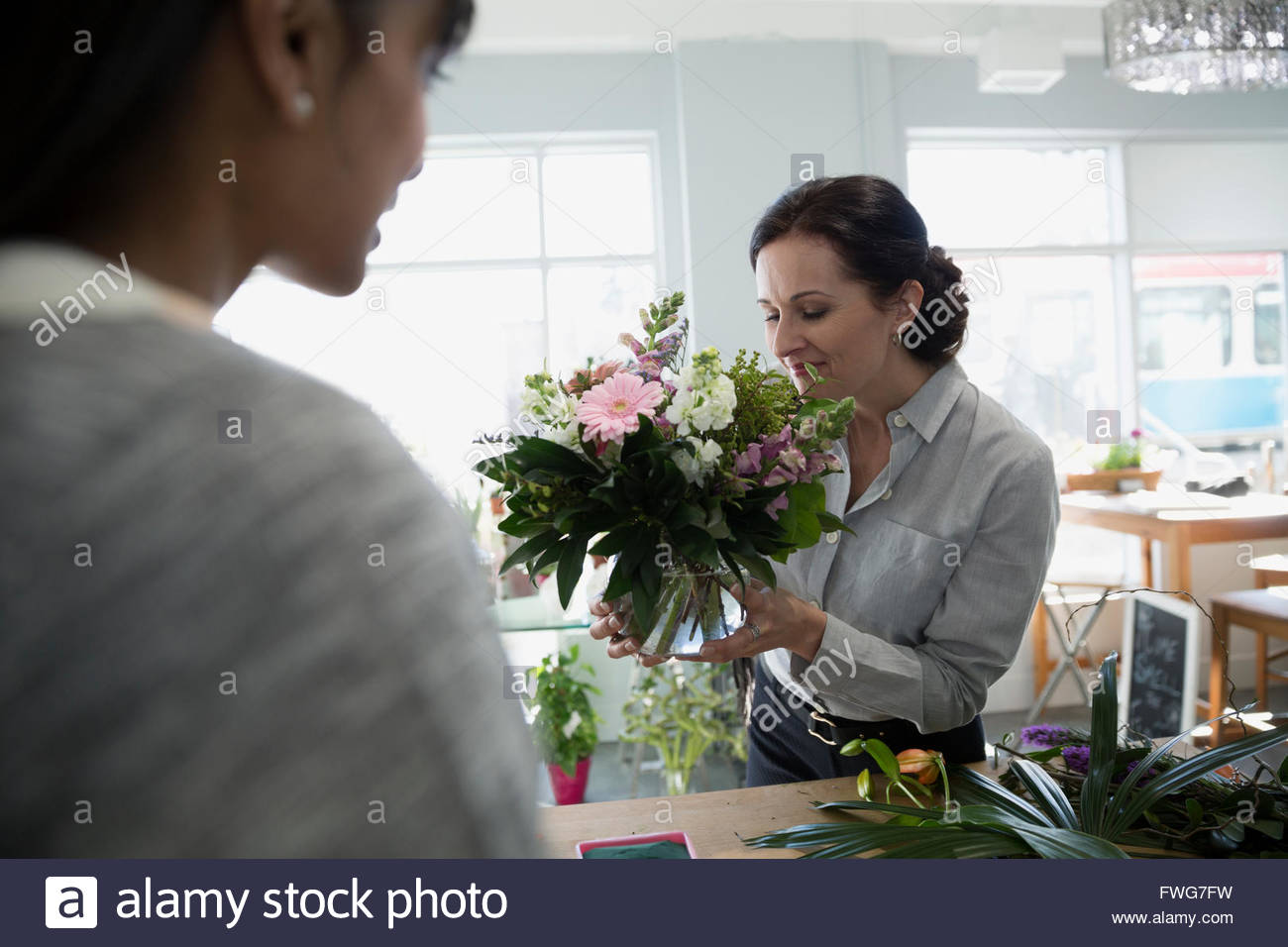 Customer smelling bouquet in flower shop - Stock Image