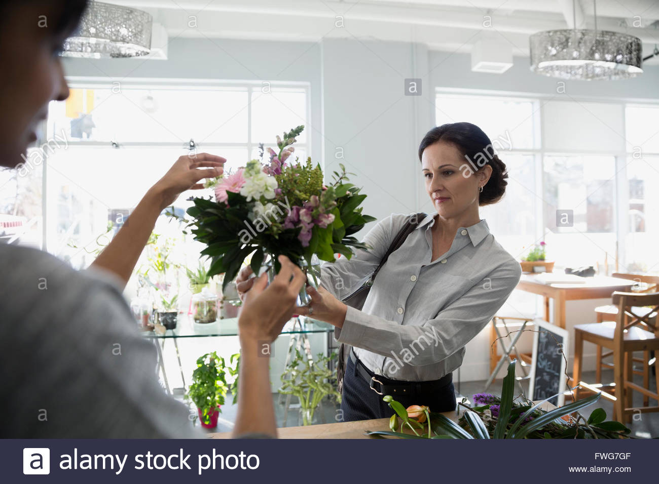 Floors presenting bouquet to customer in flower shop - Stock Image