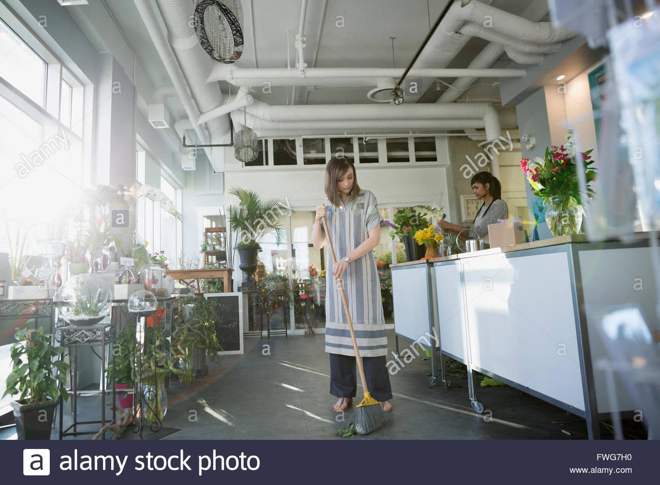 Floor sweeping floor in flower shop - Stock Image