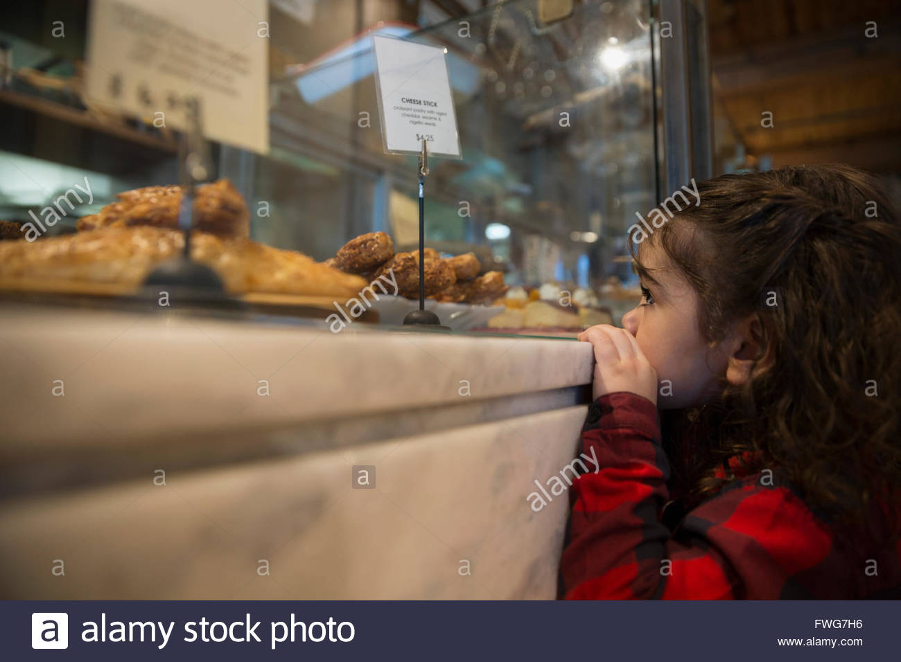 Girl eyeing pastries in bakery display case - Stock Image
