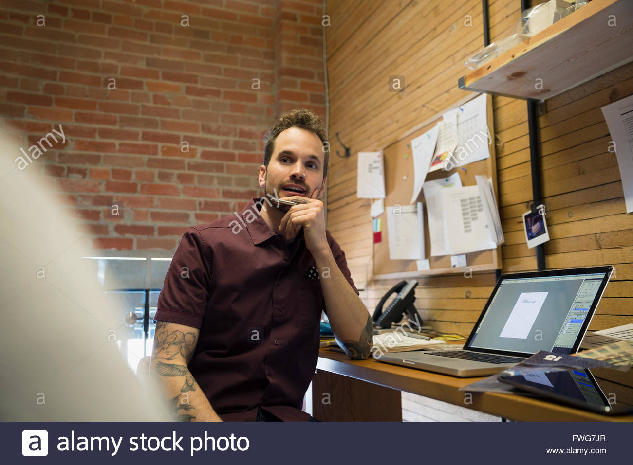 Designer listening to coworker at laptop in office - Stock Image