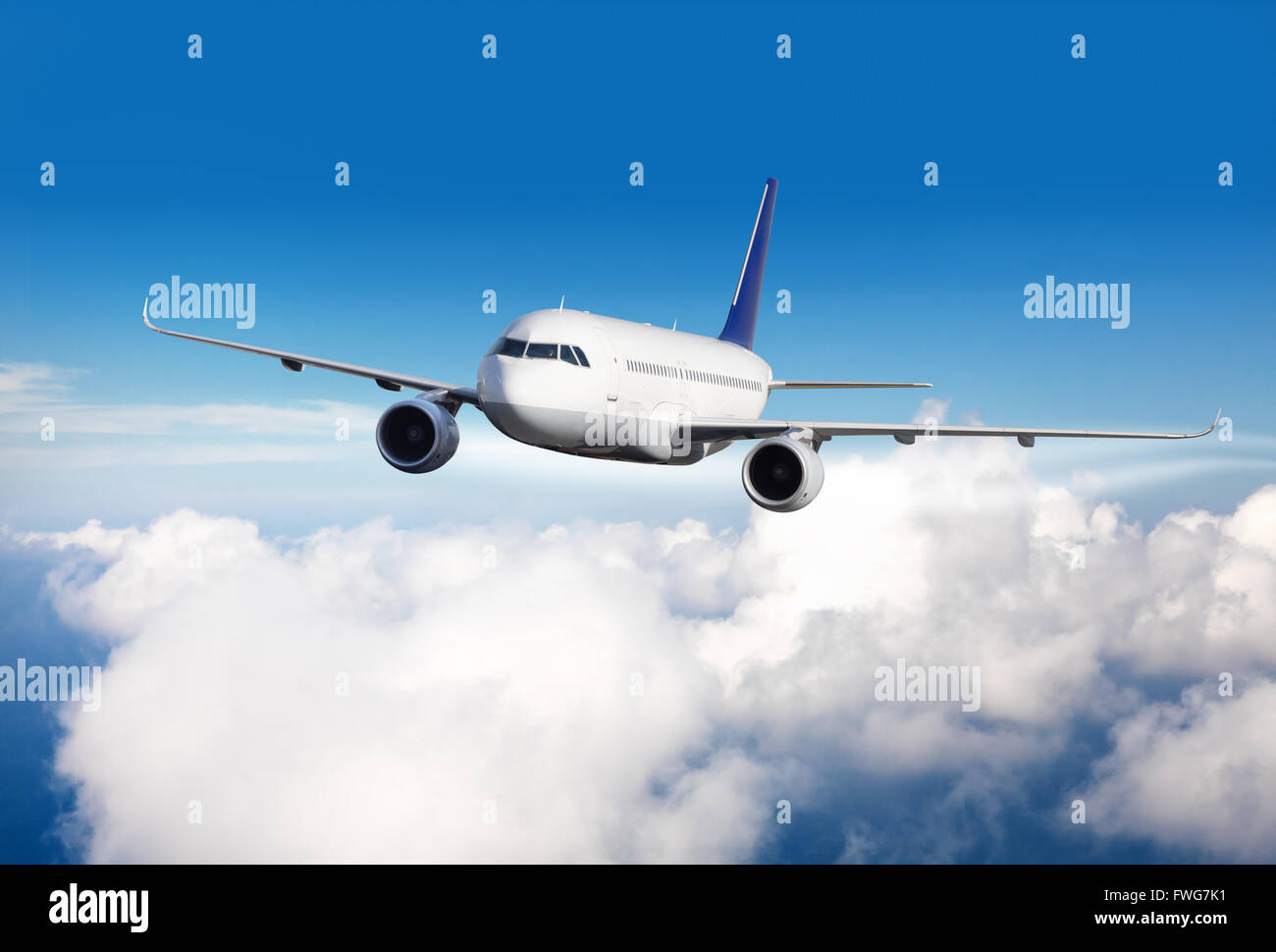 Commercial jet plane flying above clouds in day light - Stock Image