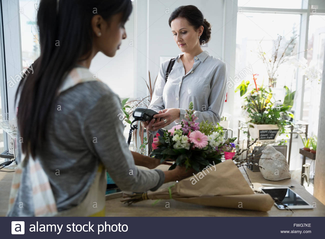 Woman paying with credit card machine flower shop Stock Photo
