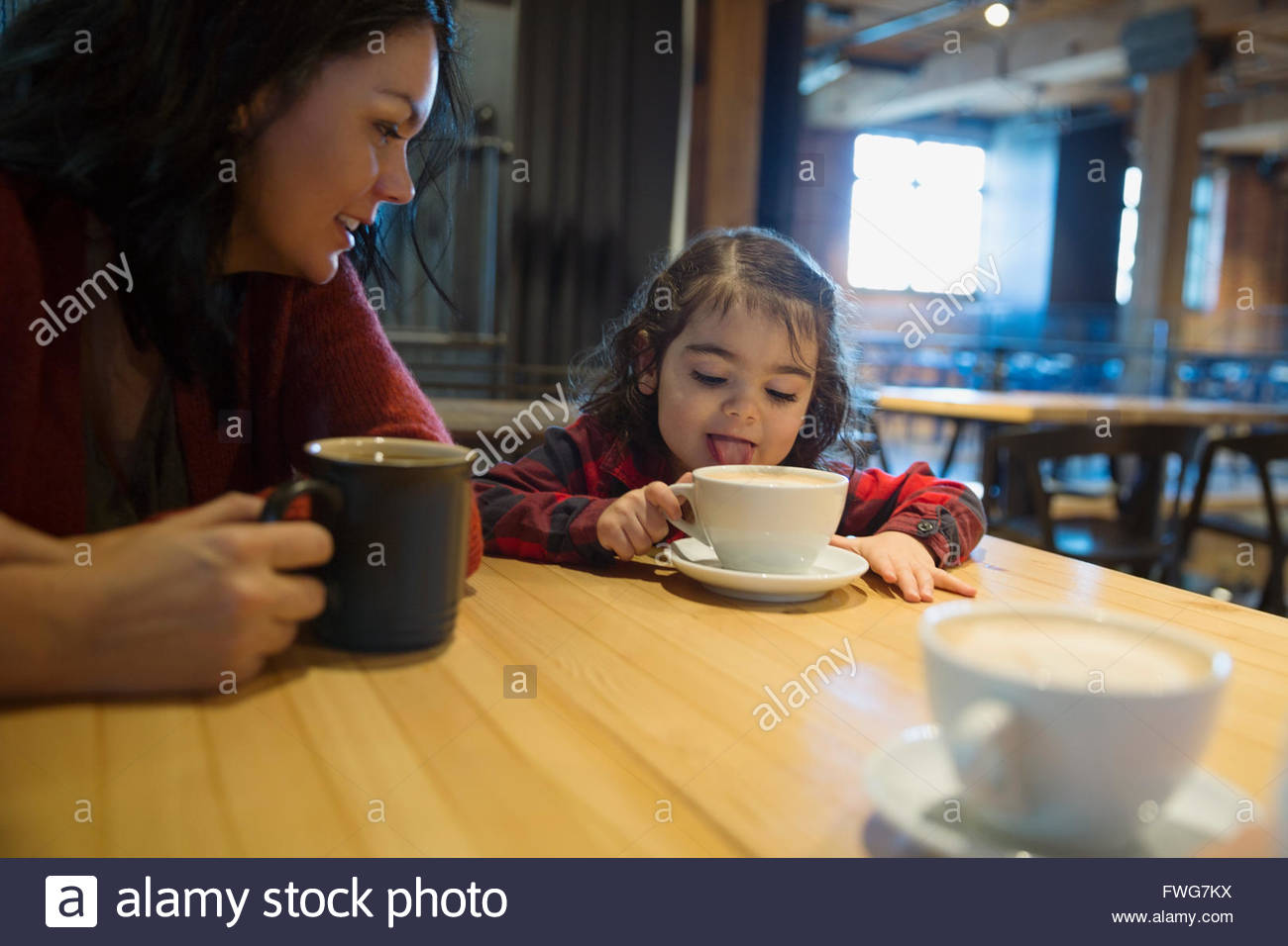 Mother watching daughter lick hot cocoa in a cafe - Stock Image