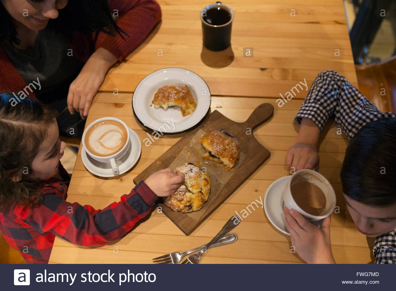 Family enjoying coffee and pastries in bakery - Stock Image