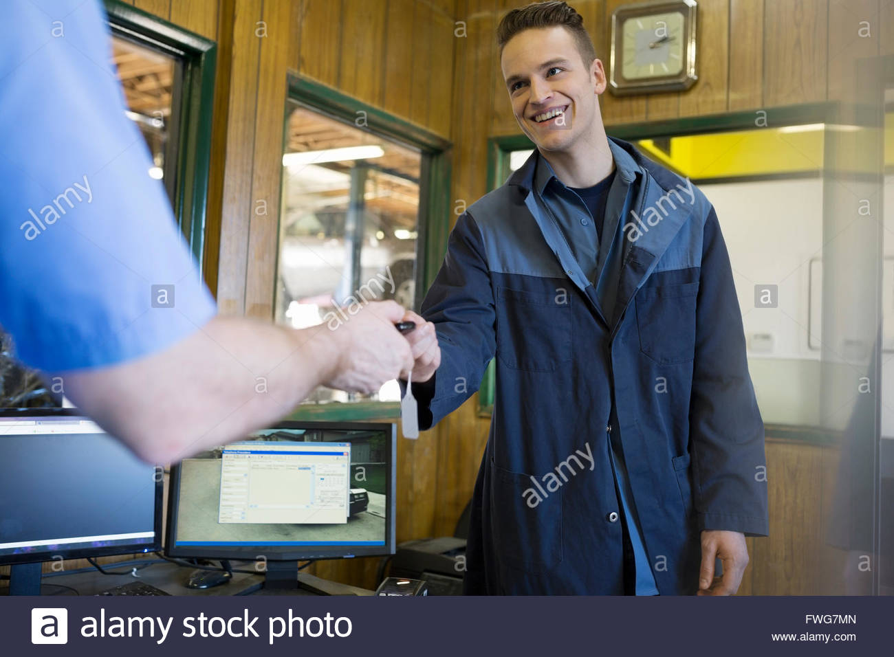 Mechanics exchanging keys auto shop office - Stock Image