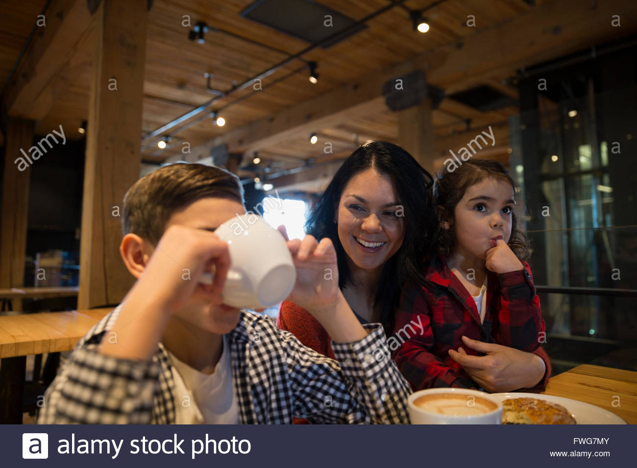 Smiling mother watching son drinking coffee in bakery Stock Photo