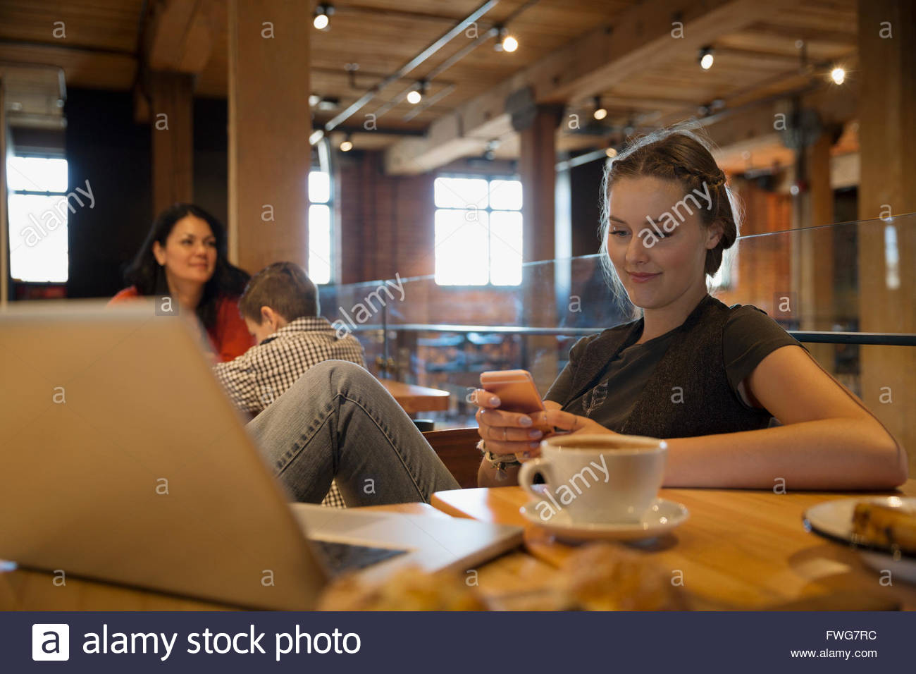 Young woman texting at laptop in cafe Stock Photo