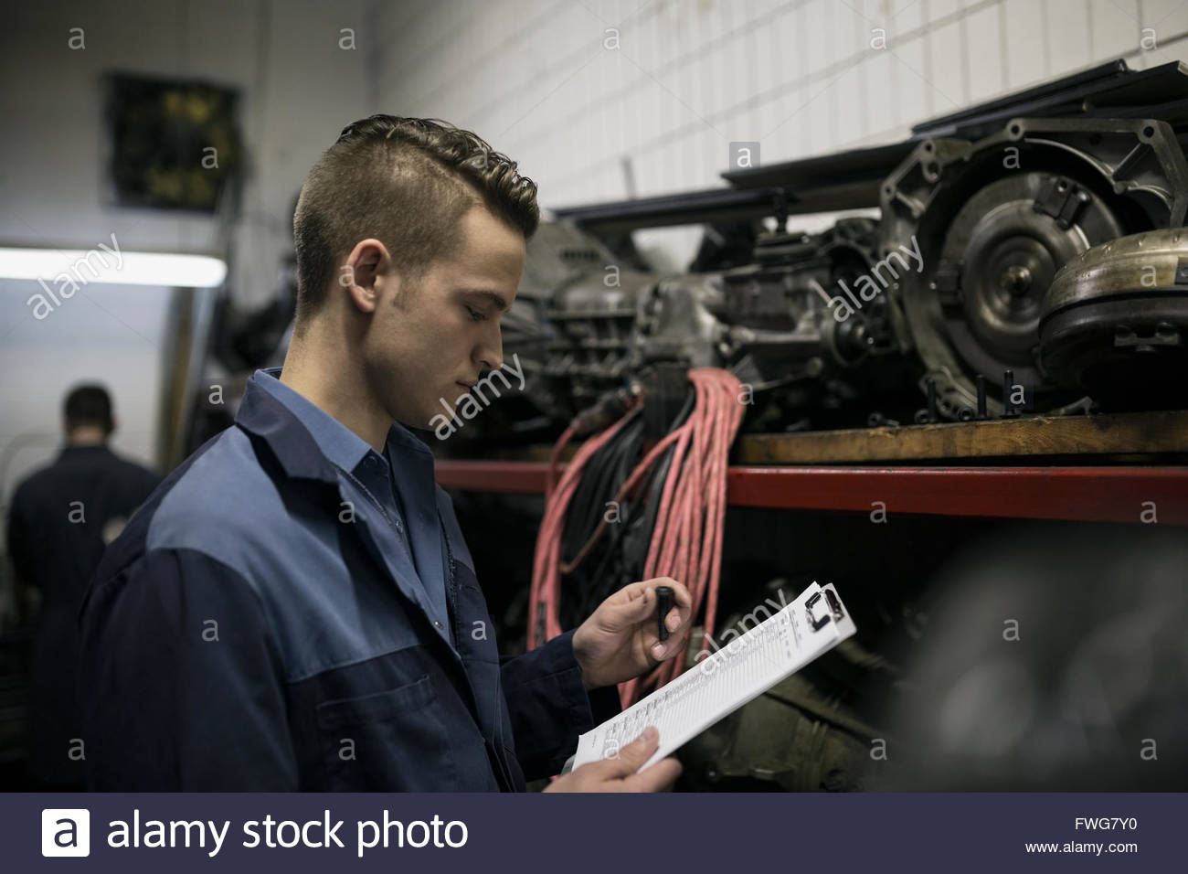 Young mechanic with clipboard examining auto parts - Stock Image