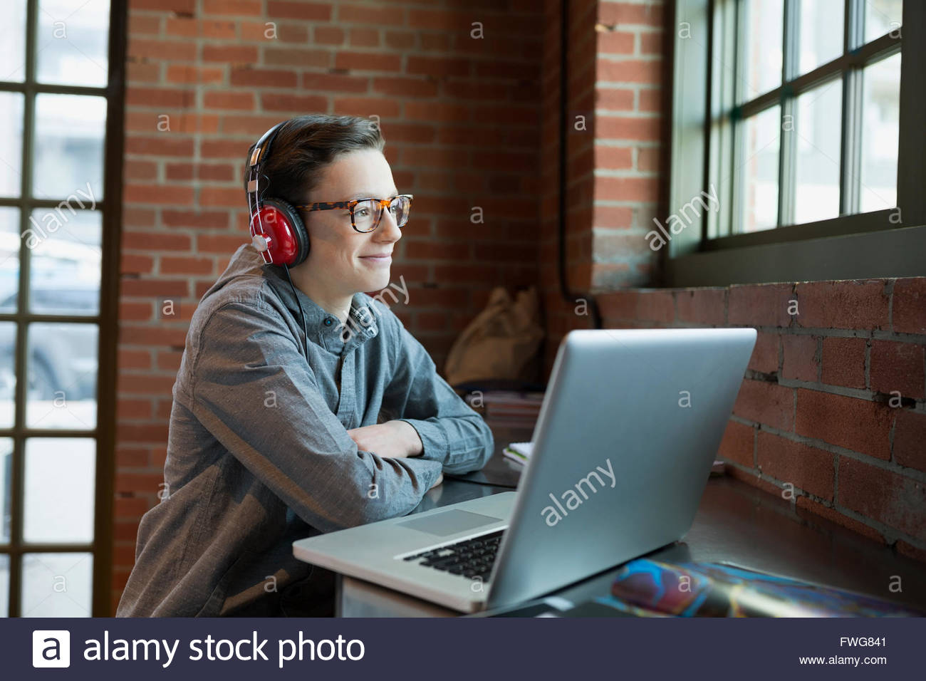 Smiling boy with headphones at laptop in coffee shop - Stock Image
