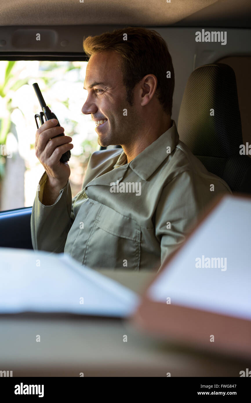 Delivery driver talking on walkie-talkie - Stock Image
