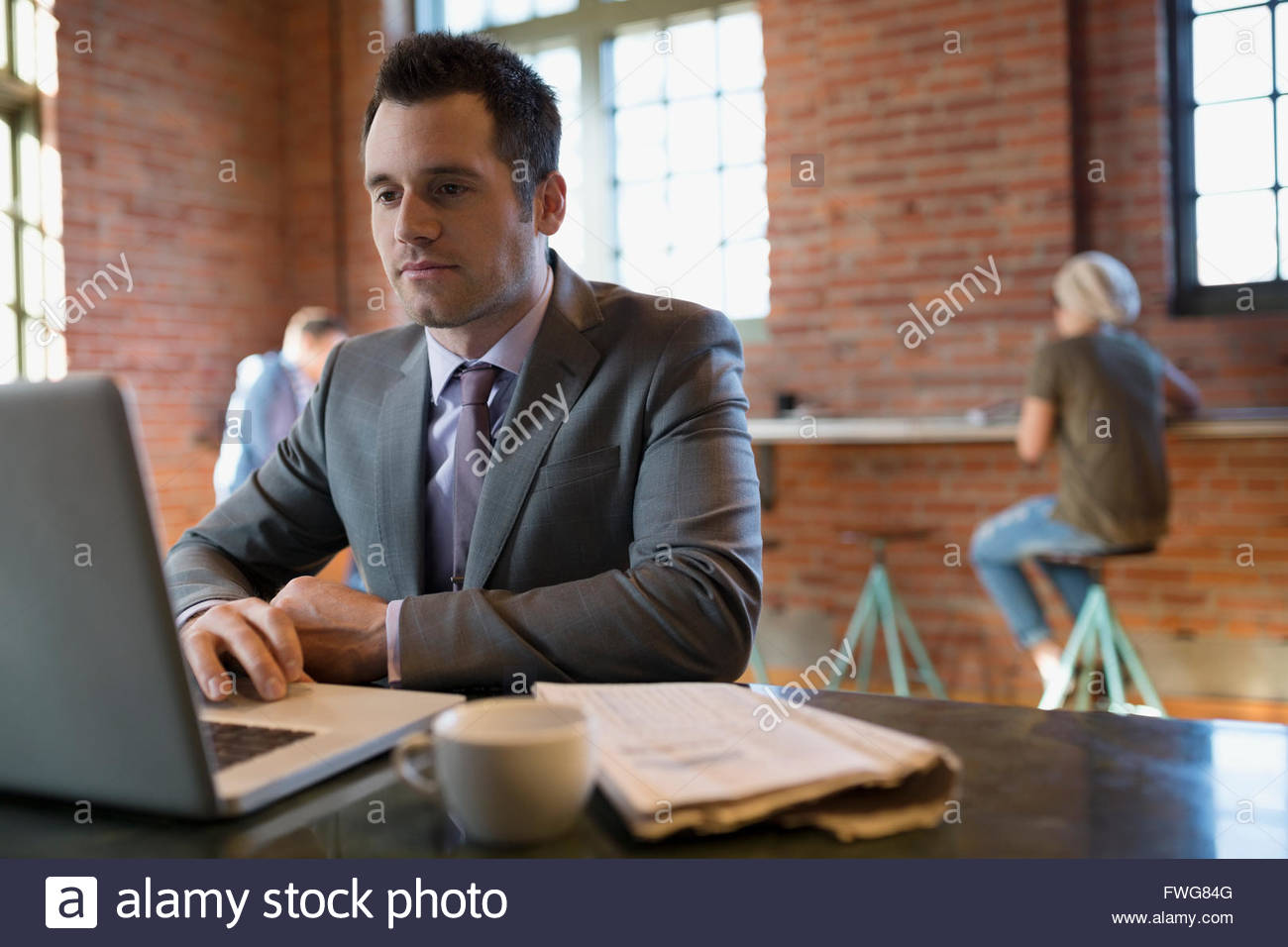 Businessman using laptop in coffee shop - Stock Image