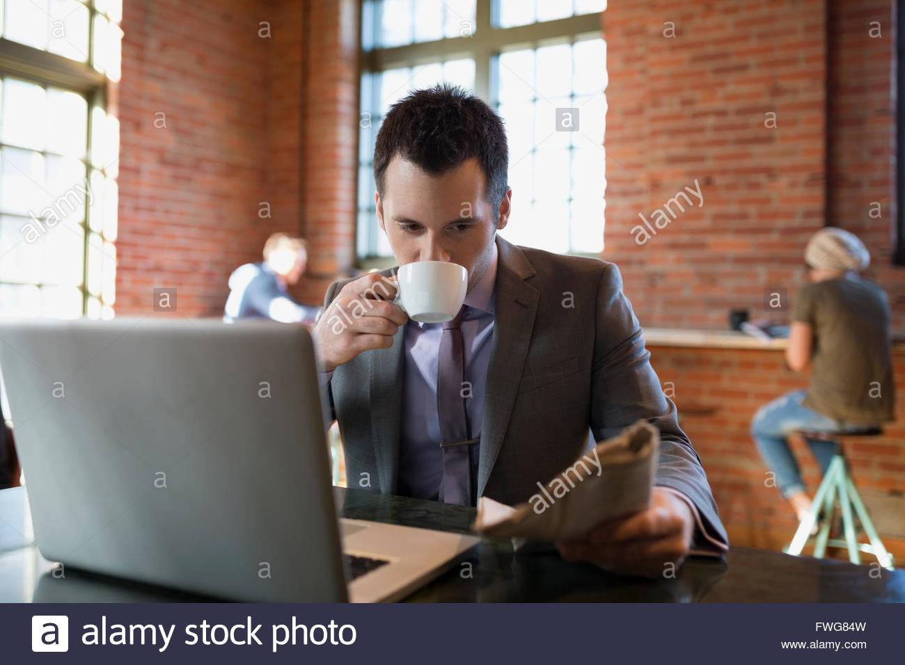 Businessman drinking coffee reading newspaper coffee shop - Stock Image