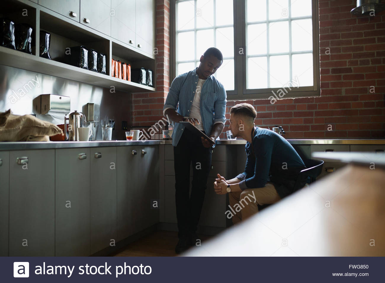 Entrepreneurial coffee roasters with clipboard in kitchen - Stock Image