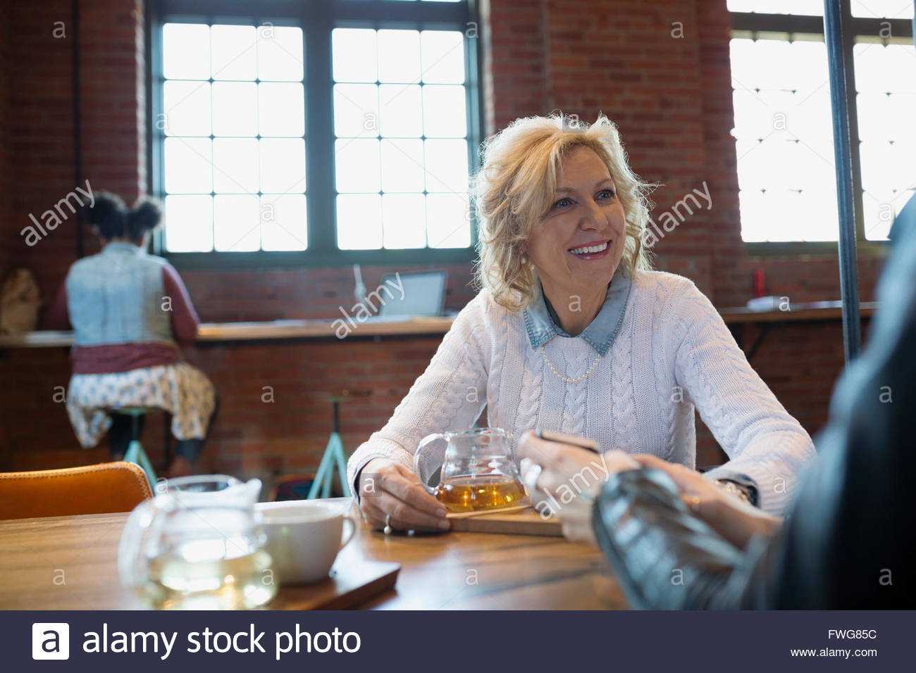 Smiling woman drinking tea at coffee shop - Stock Image