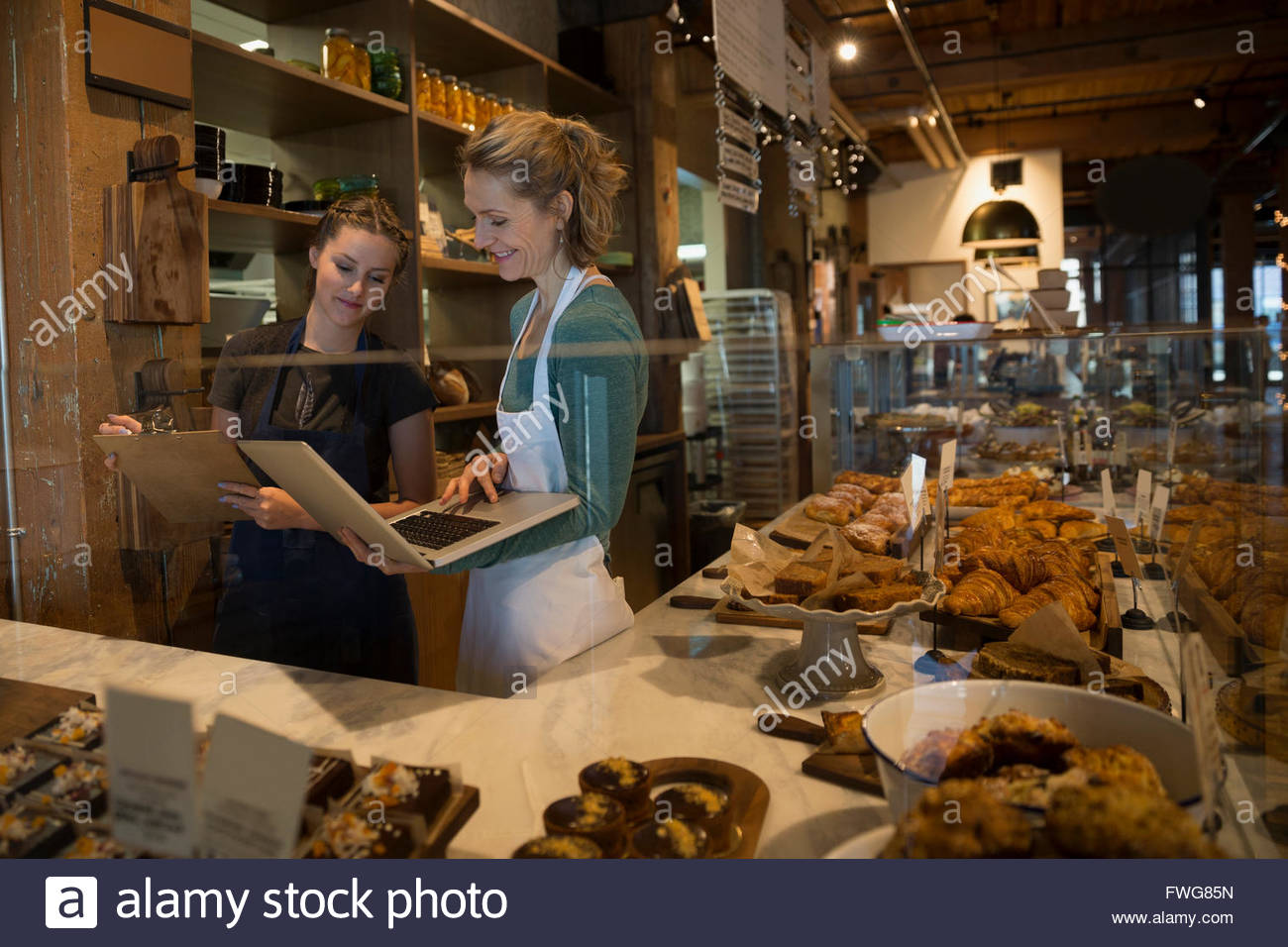Bakery owner and worker with laptop and clipboard - Stock Image