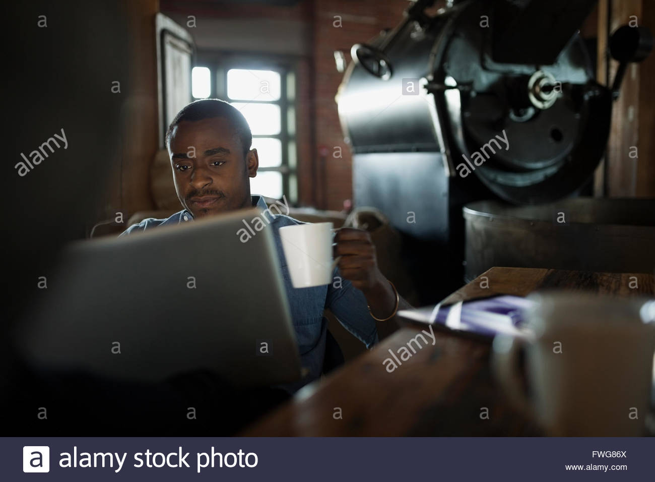 Coffee roaster using laptop and drinking coffee - Stock Image