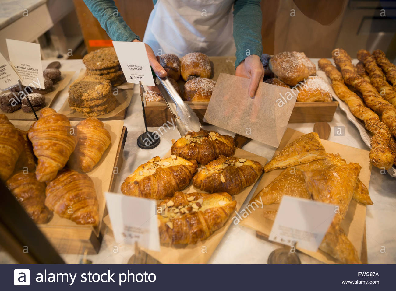 Bakery owner serving croissant - Stock Image