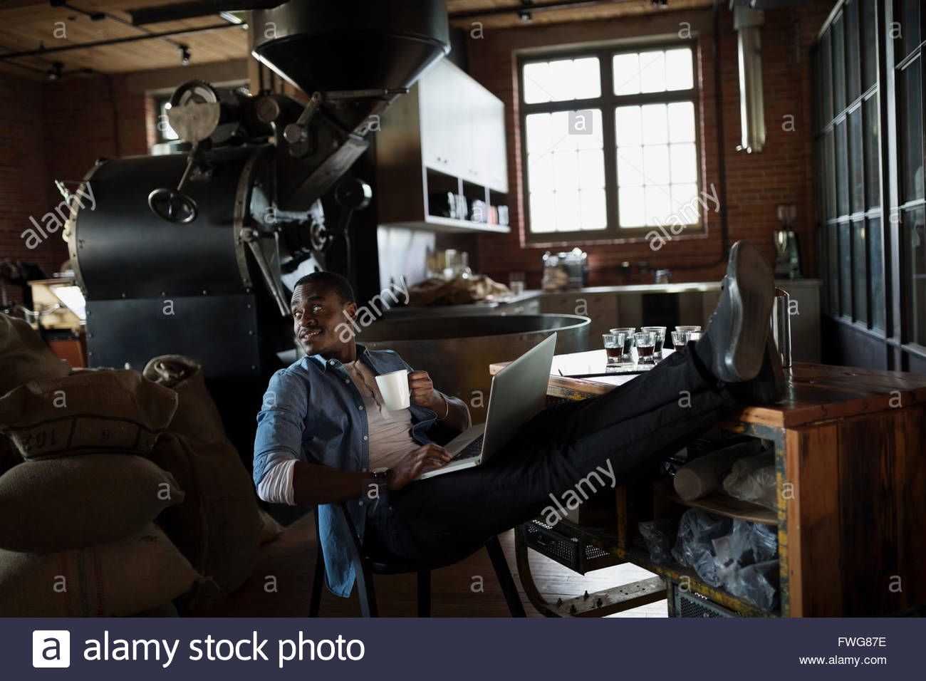 Coffee roaster using laptop drinking coffee with feet up - Stock Image