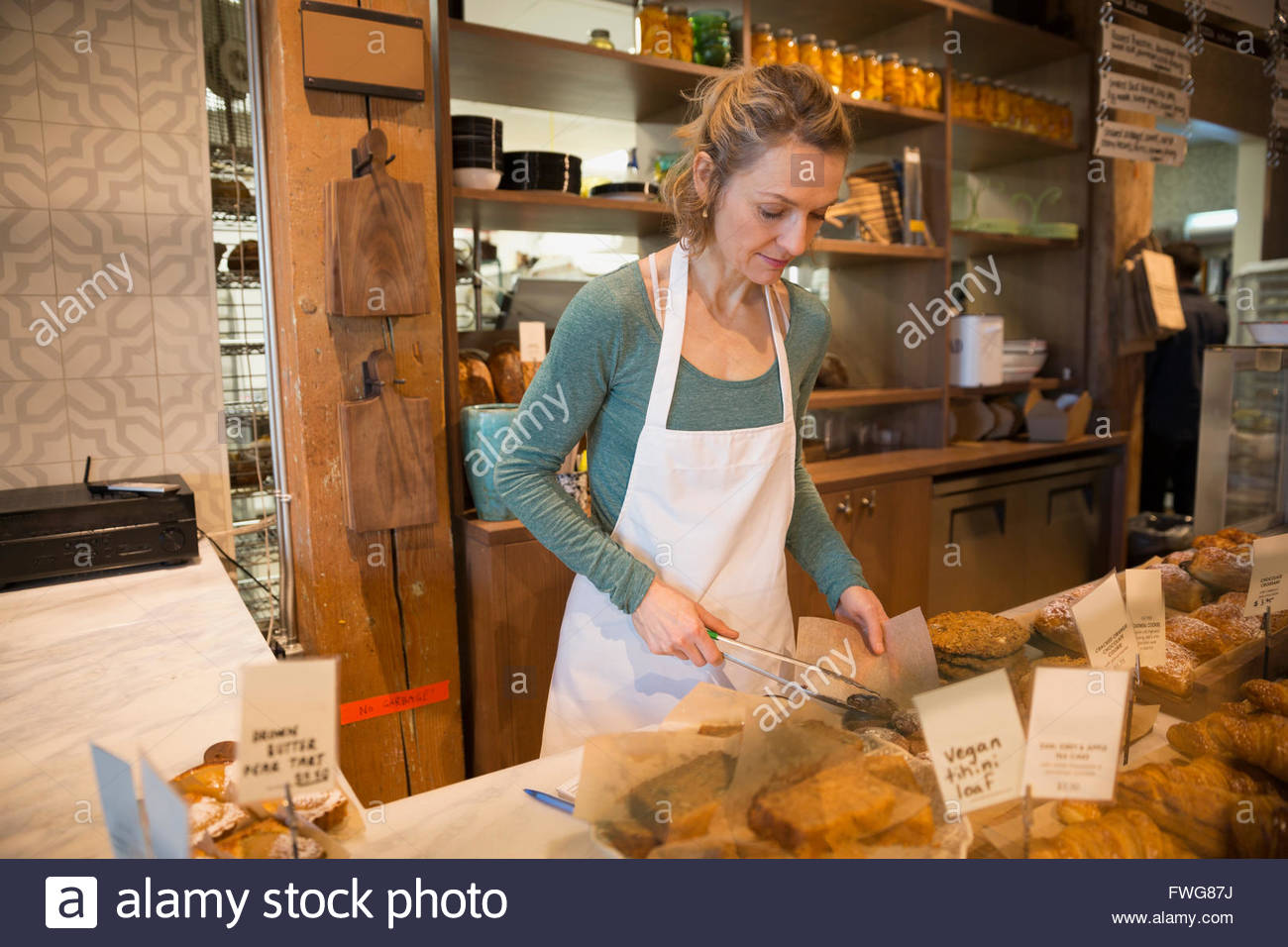 Bakery owner working behind counter - Stock Image