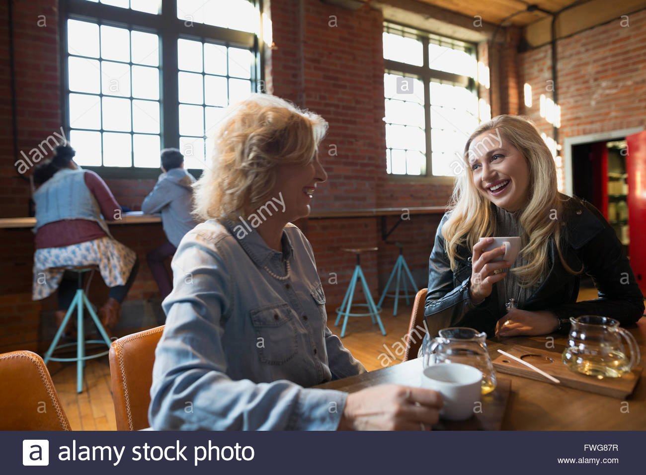 Mother and daughter drinking tea talking in coffee shop - Stock Image