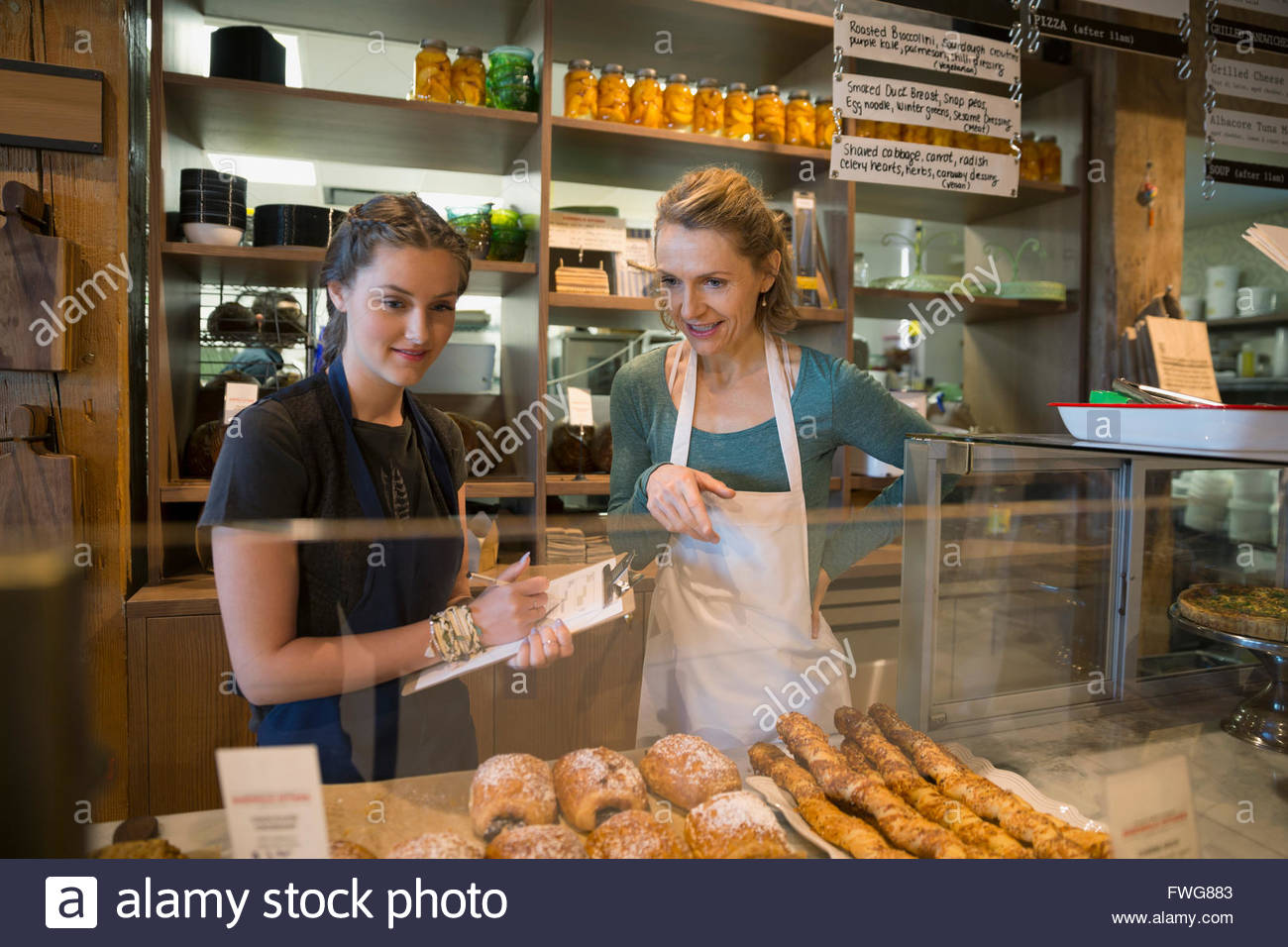 Bakery owner and worker with clipboard display case - Stock Image