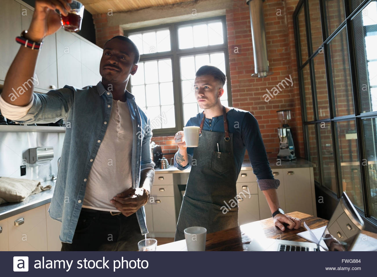 Entrepreneurial coffee roasters examining coffee in kitchen - Stock Image