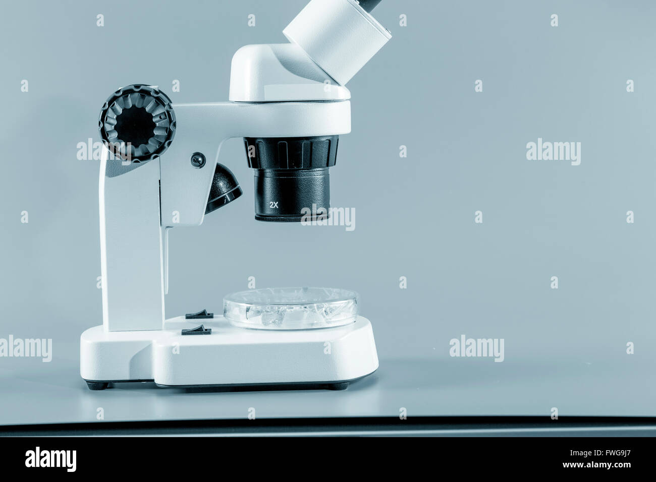 Monocular microscope against a grey background. - Stock Image