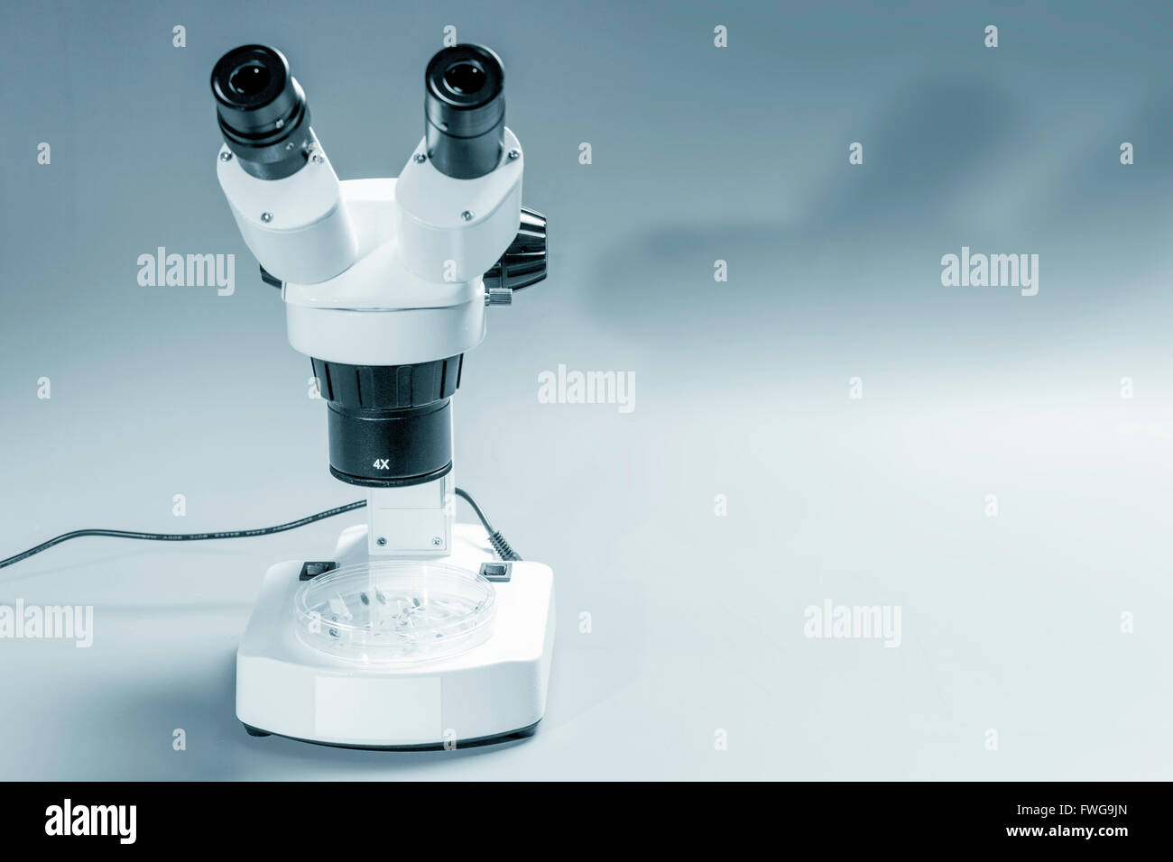 Medical microscope against a grey background. - Stock Image