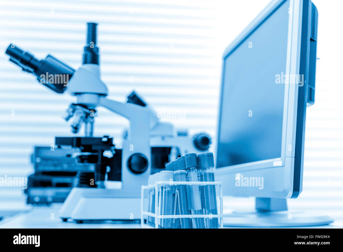 Microscope and computer monitor in the laboratory. - Stock Image