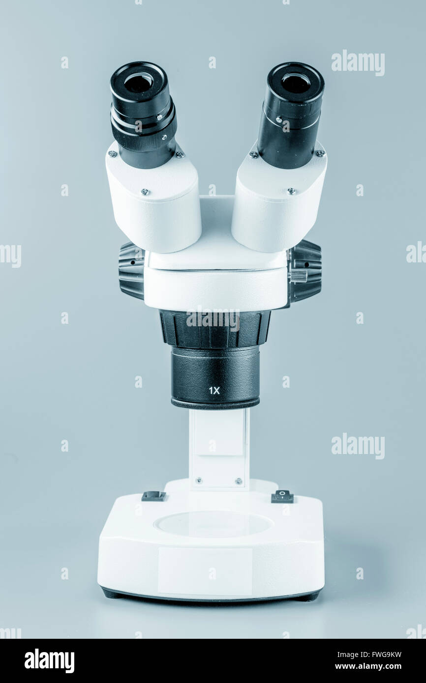 Laboratory microscope against a grey background. - Stock Image
