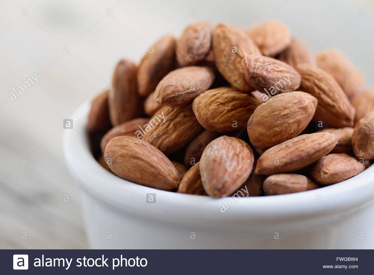 Bowl of almond nuts on rustic wooden table in natural light. - Stock Image