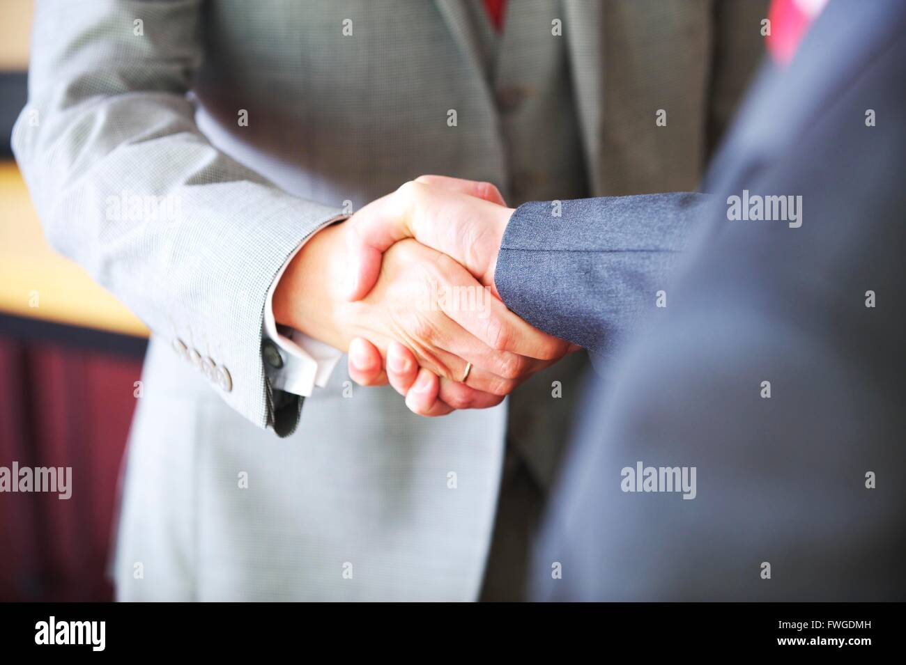 UK Business men in the city shake hands to seal the contract - Stock Image