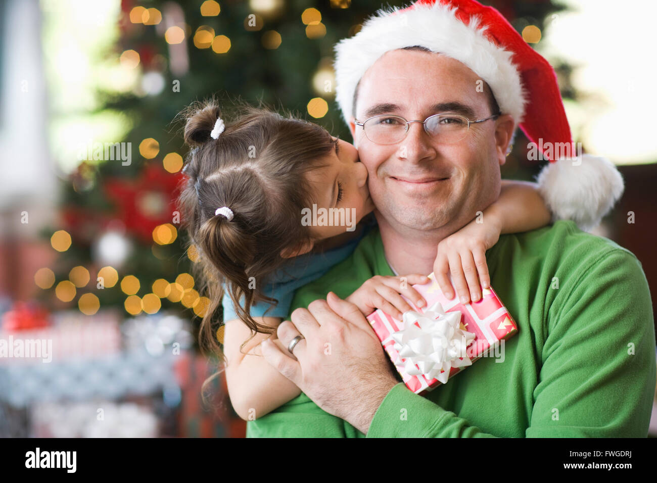A Man And Girl Father Daughter Hugging Exchanging Presents By Christmas Tree