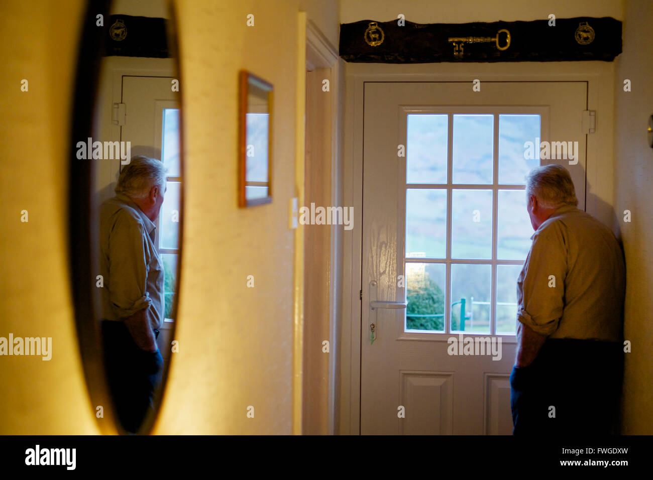 An Elderly Man Standing By A Door Looking Out Through The Window Panes.