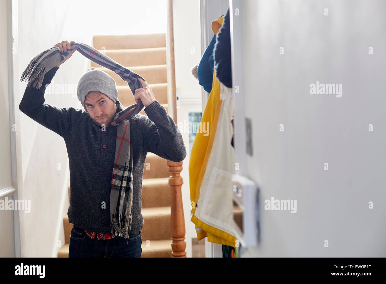 A man in a winter coat, hat and scarf arriving home, taking his scarf off. - Stock Image