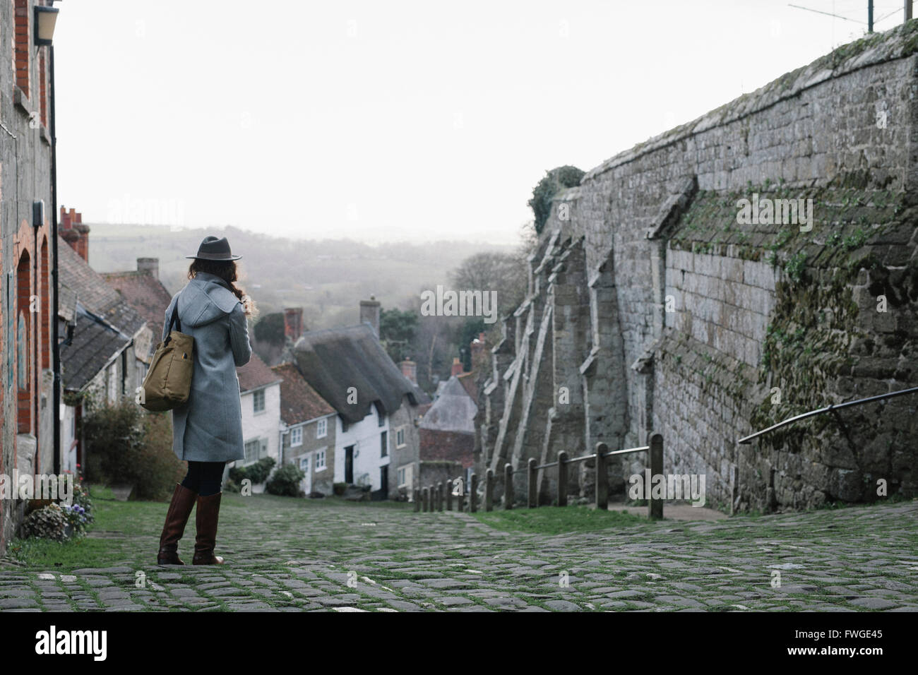 A woman at the top of Gold Hill, a steep cobbled street in Shaftesbury. - Stock Image
