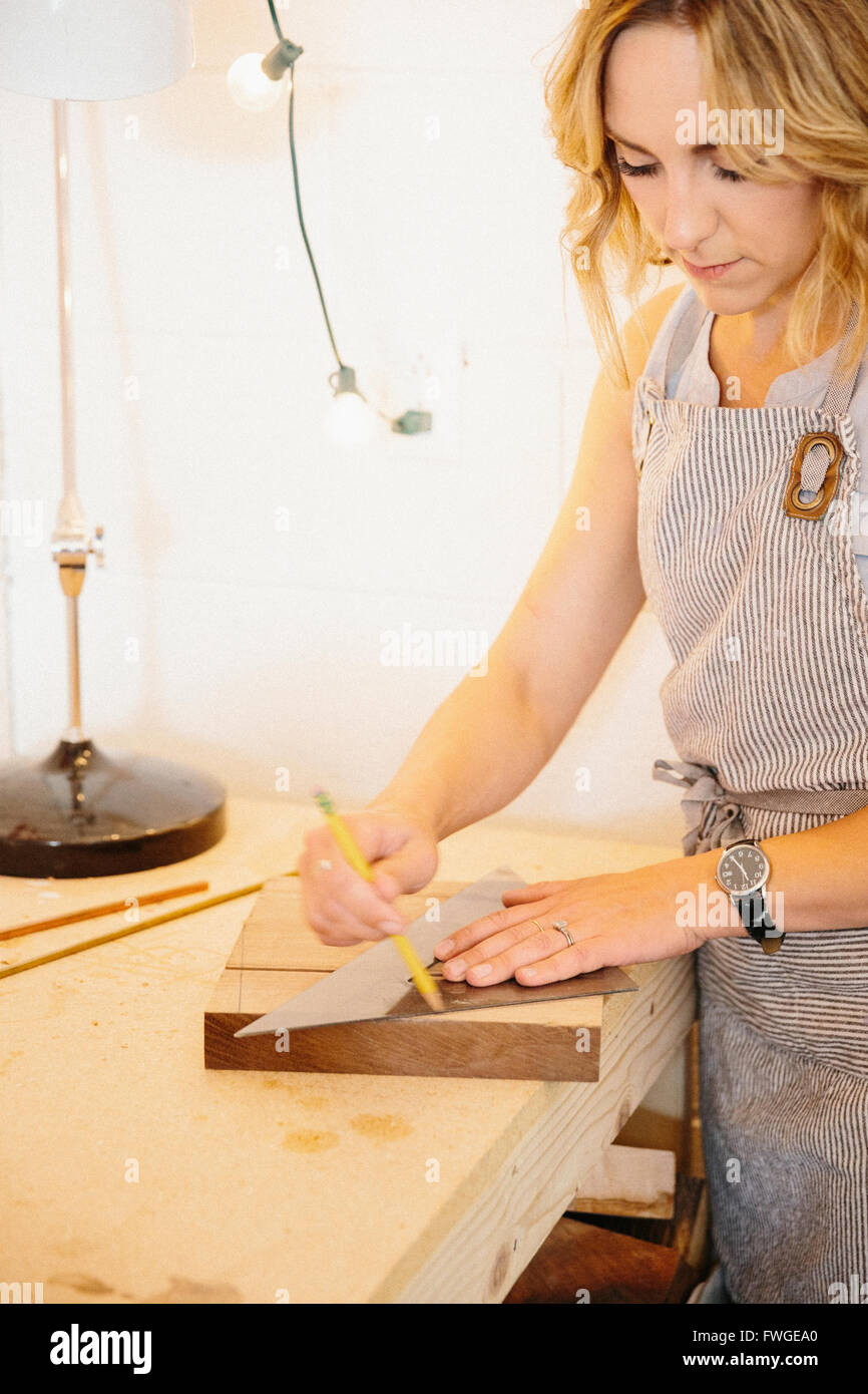 A woman in her workshop using a template to mark wooden blocks. - Stock Image