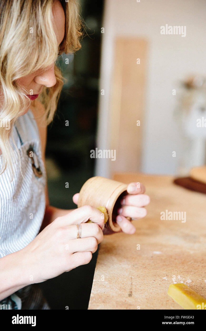 A woman in a workshop using a slab of wax to oil a small wood turned cup or bowl - Stock Image
