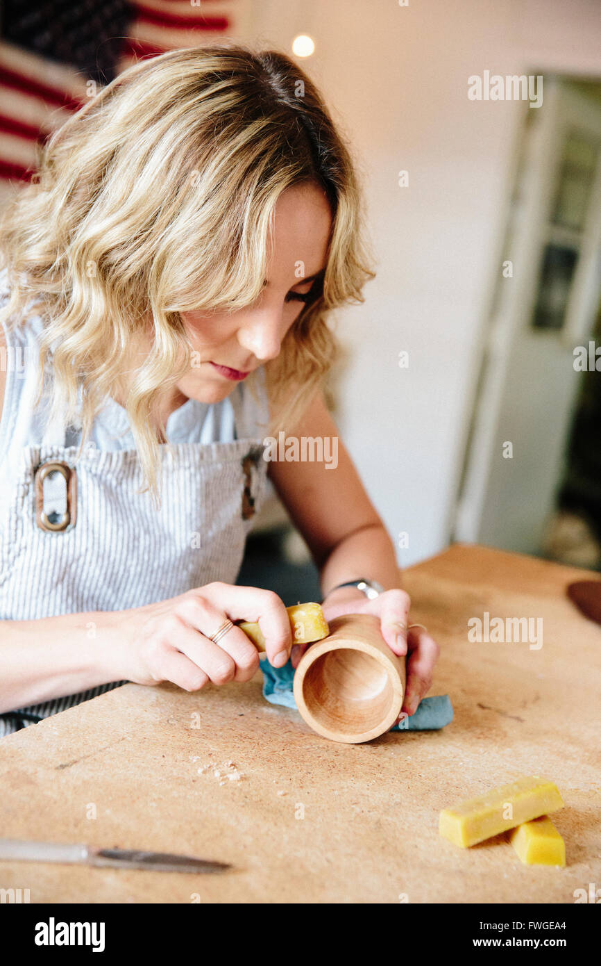 A woman in a workshop using a slab of wax to oil a small wood turned cup or bowl. - Stock Image