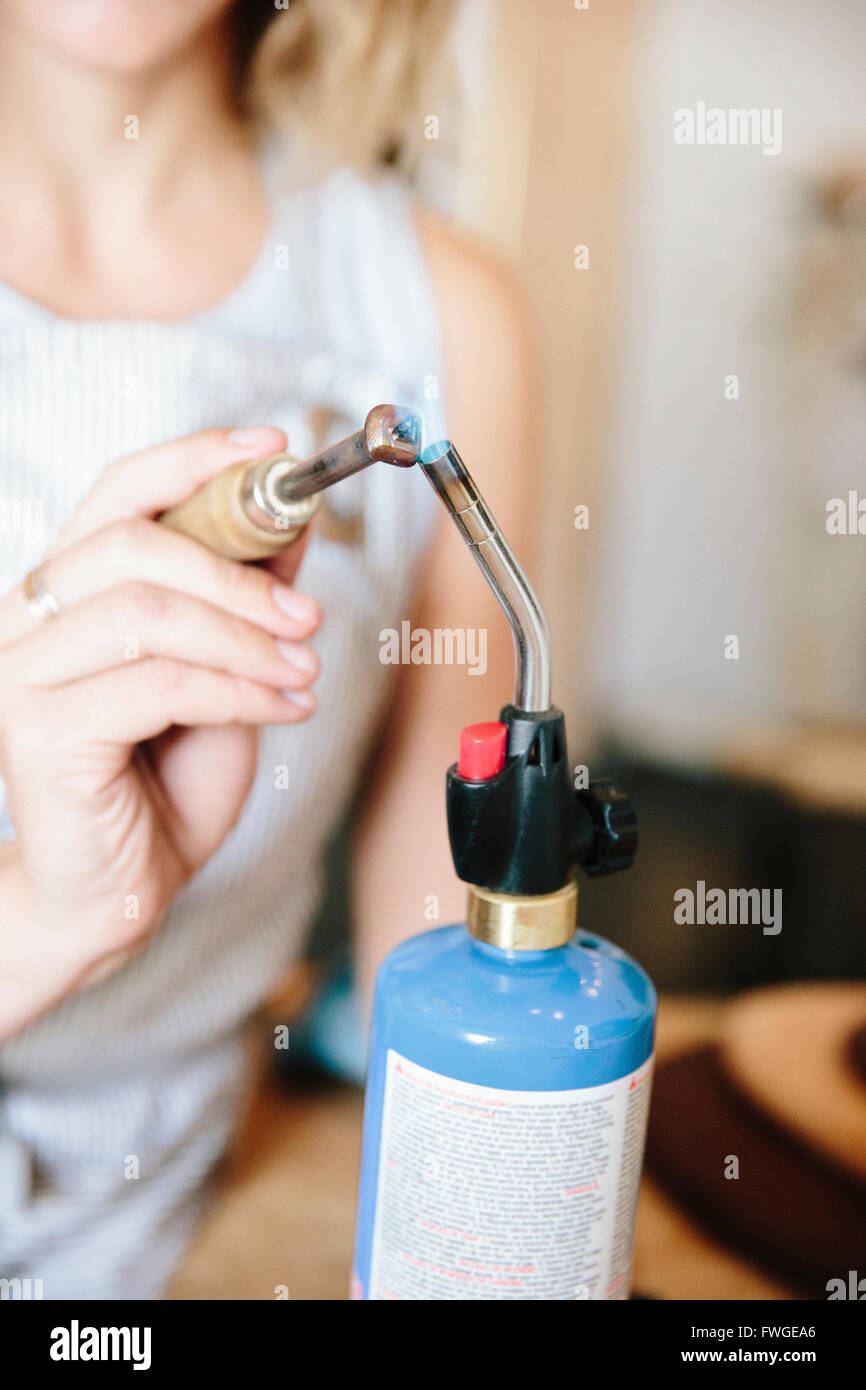 A woman holding a hand tool to the flame of a blow torch, heating metal. - Stock Image