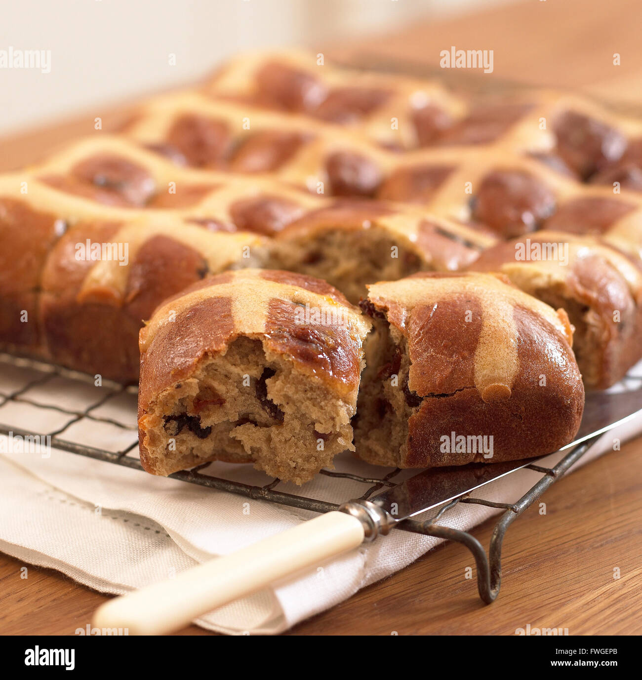 Hot cross buns on a cooling rack. - Stock Image