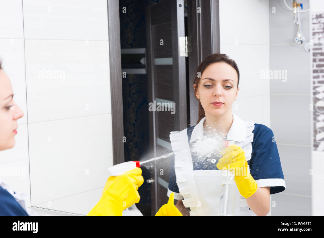 Reflection of serious young adult female maid squirting glass cleaner on mirror while working in hotel bathroom - Stock Image