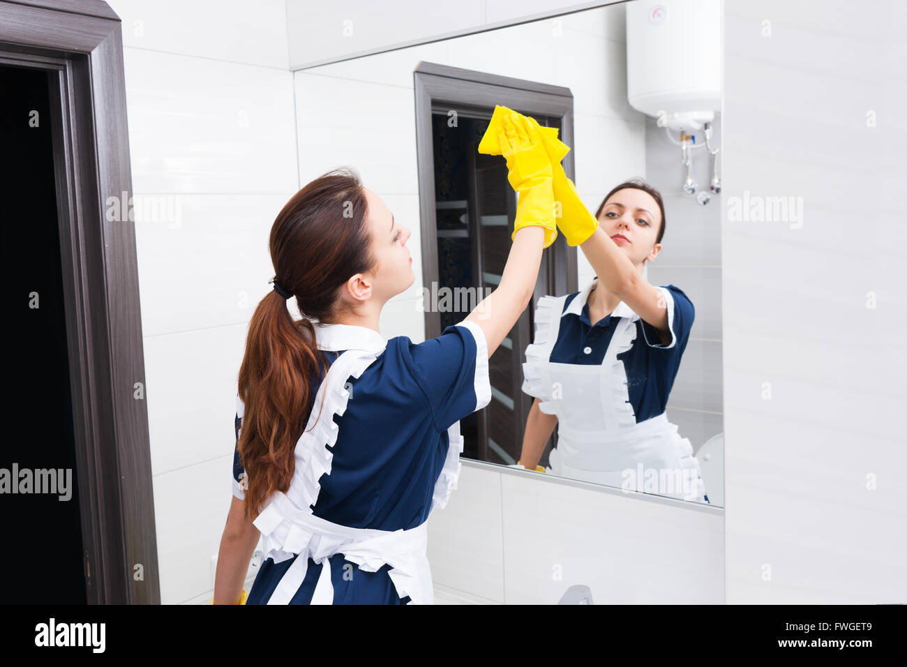 Single young adult female hotel maid using yellow sponge and rubber gloves to clean up high section of mirror while - Stock Image